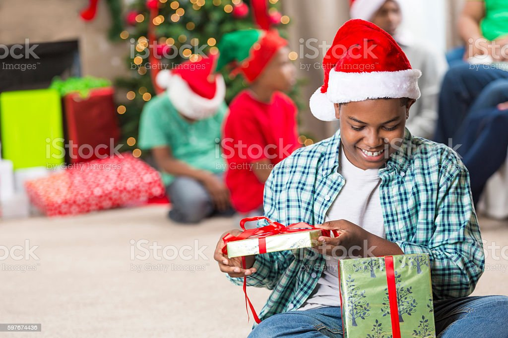 African American boy peeks inside Christmas gift stock photo