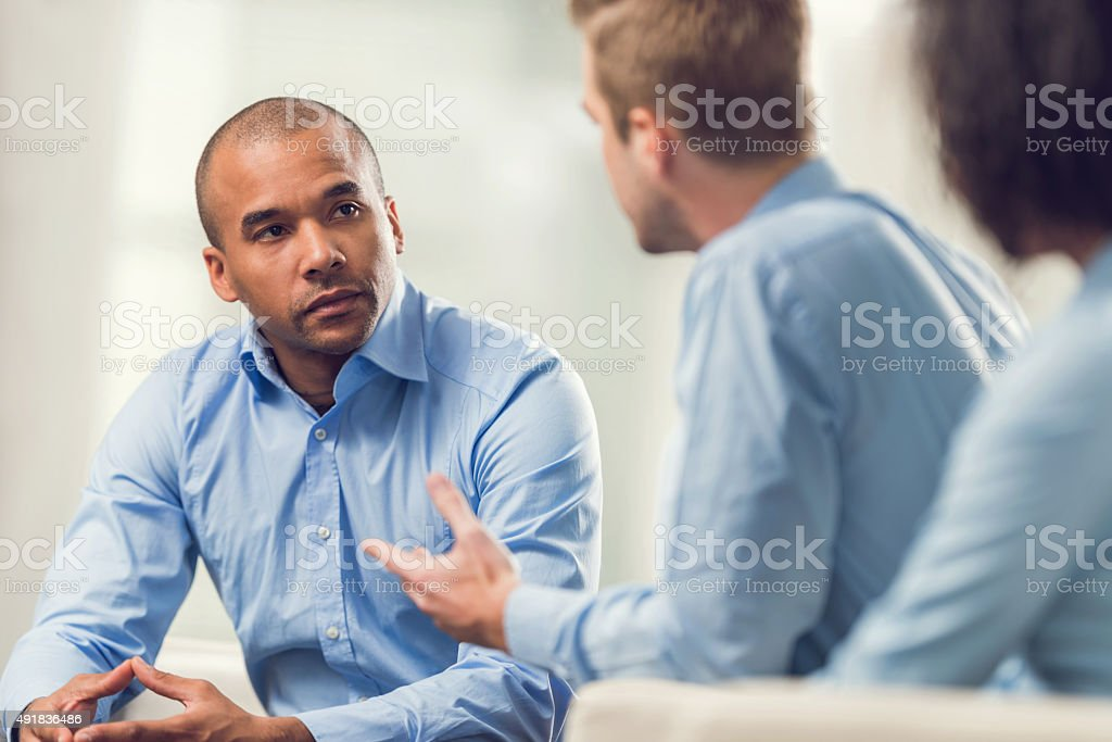 African American businessman discussing with his colleagues. stock photo