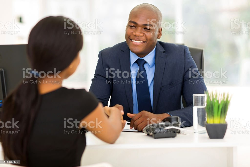african american businessman handshaking with client stock photo