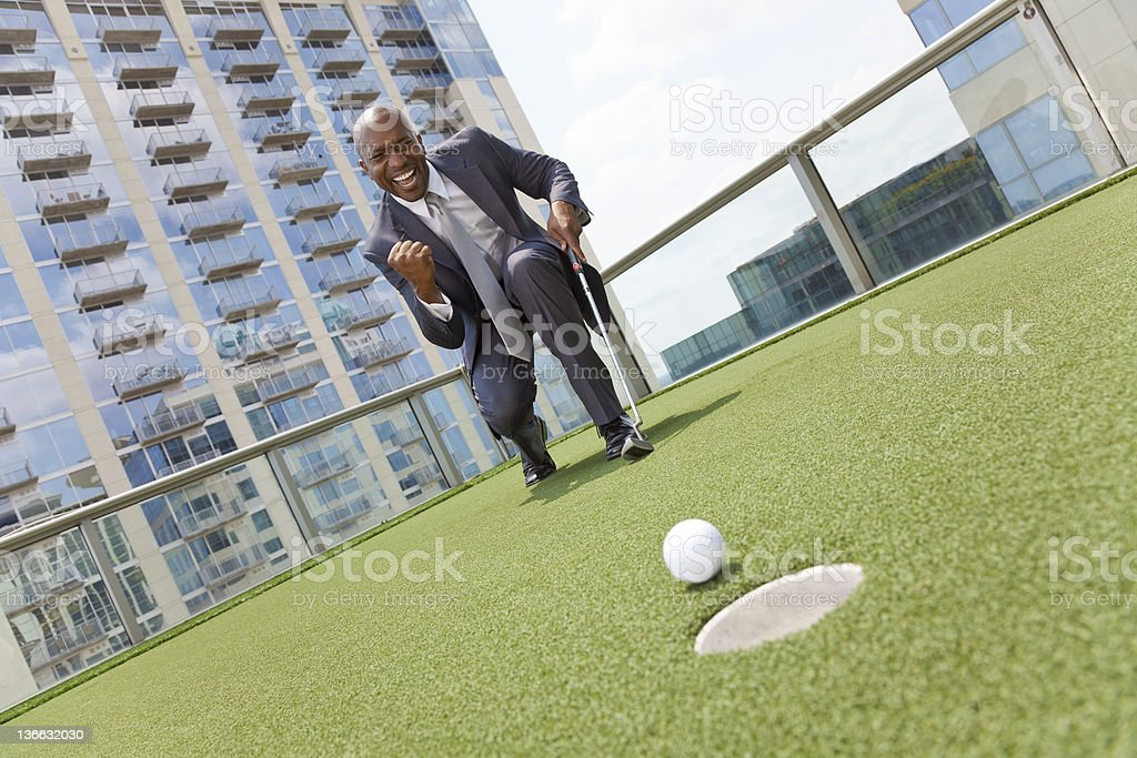 African American Businessman Playing Golf on Skyscraper Rooftop royalty-free stock photo