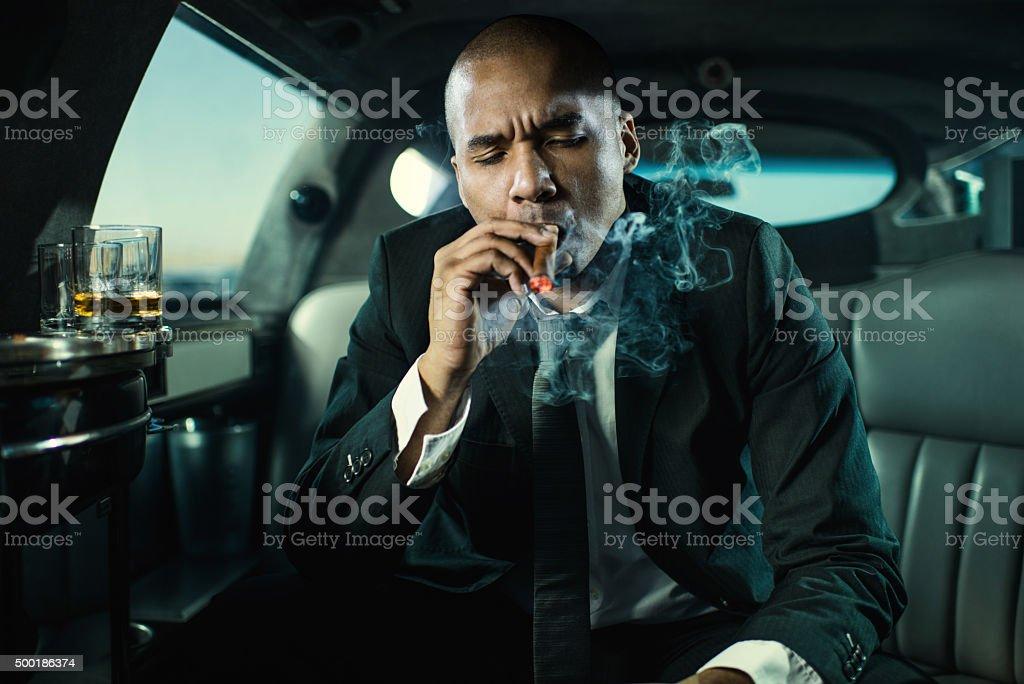 African American businessman smoking Cuban cigar in limousine. stock photo