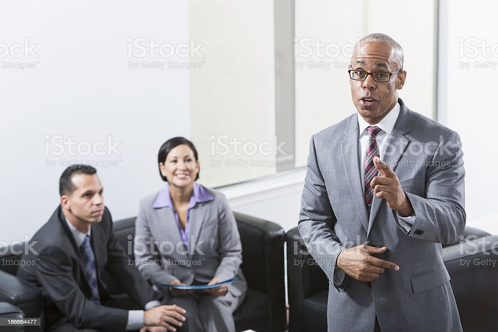 African American businessman talking, colleagues listening in background royalty-free stock photo