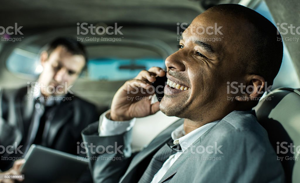 African American businessman talking on cell phone in a limousine. stock photo
