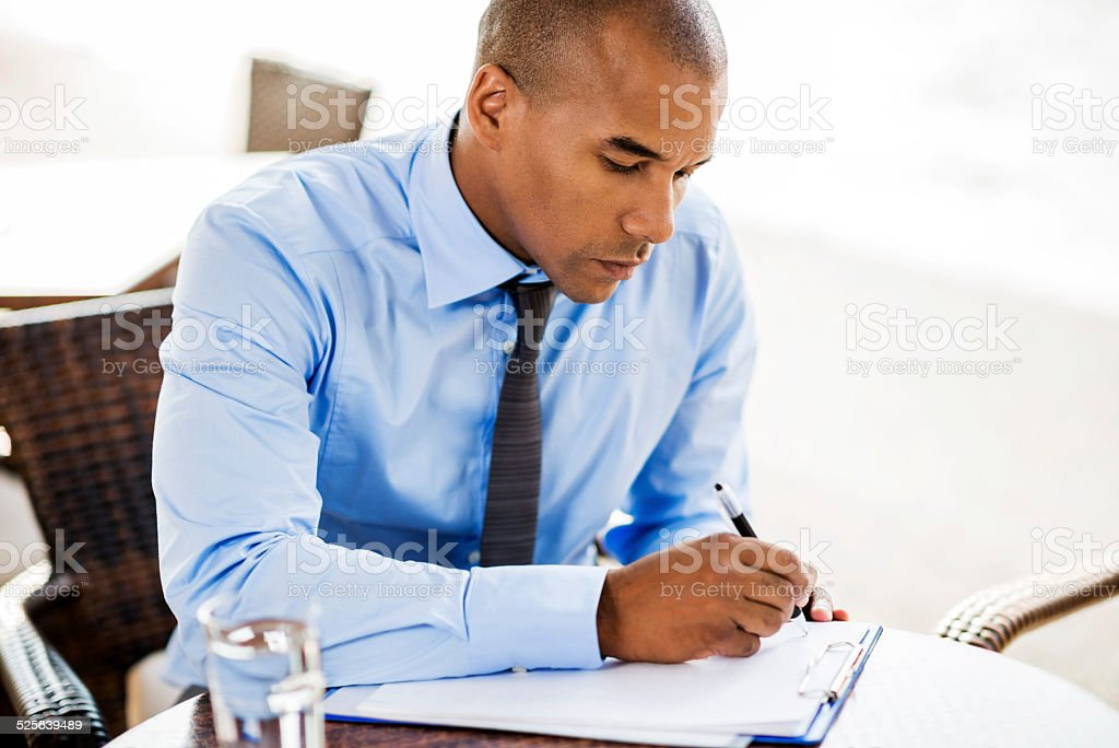African American businessman writing a document outdoors. stock photo