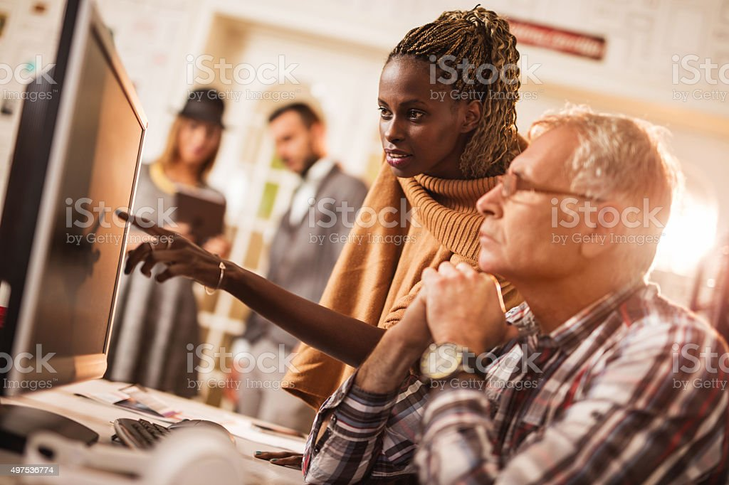 African American businesswoman and mature businessman working on desktop PC. stock photo