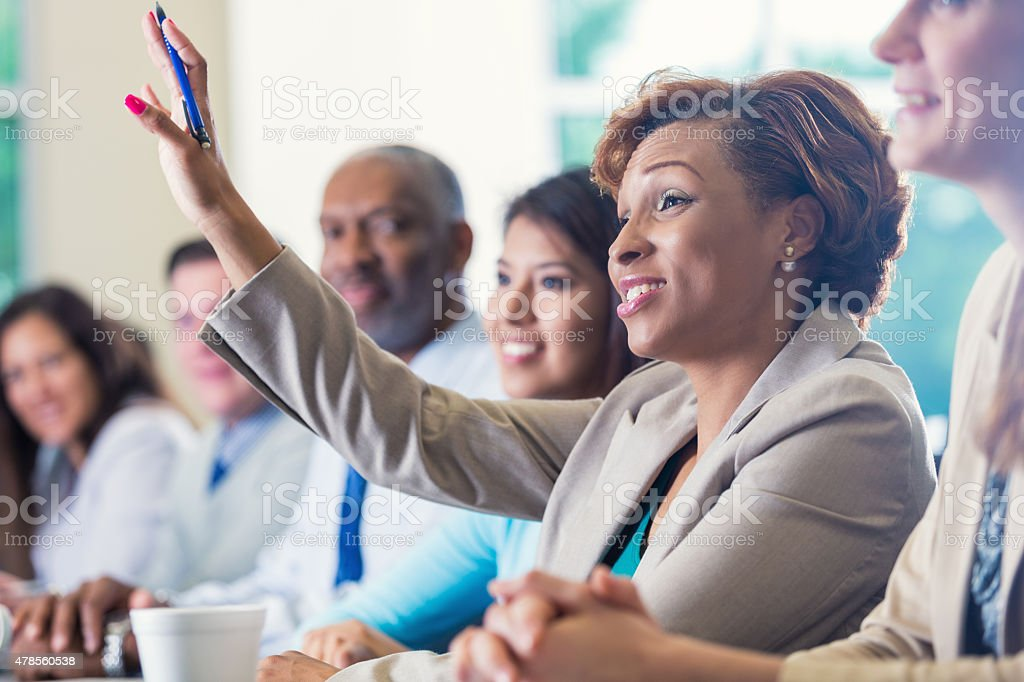 African American businesswoman raising hand, asking question in business conference stock photo