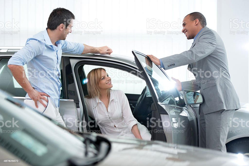 African American car salesperson talking with his customers. stock photo