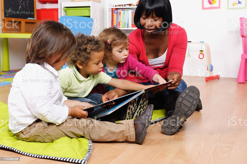 African American Carer And Group Of Little Children Reading Story royalty-free stock photo