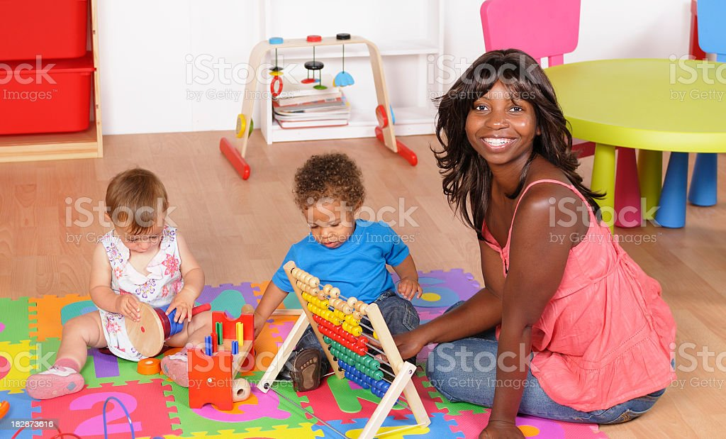 African American Carer And Pair Of Babies At Playtime stock photo
