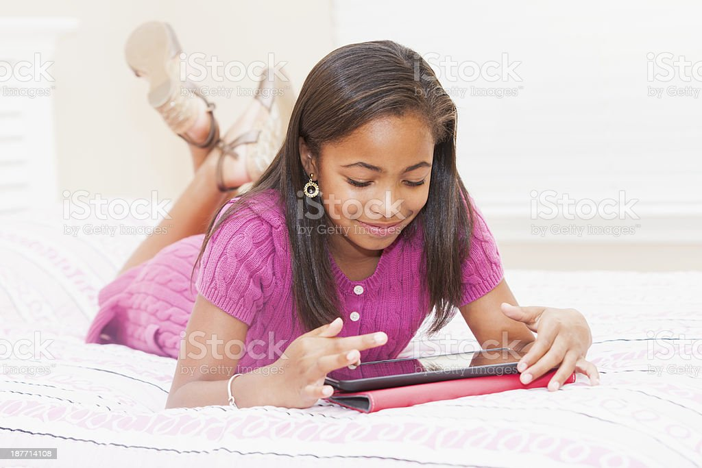 African American child at home in bedroom using digital tablet stock photo