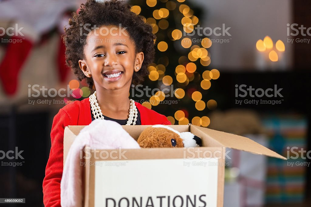 African American child holding box of toy donations at Christmastime stock photo