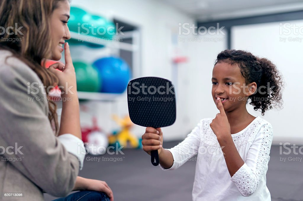 African American child holding mirror and touching lips for therapy stock photo