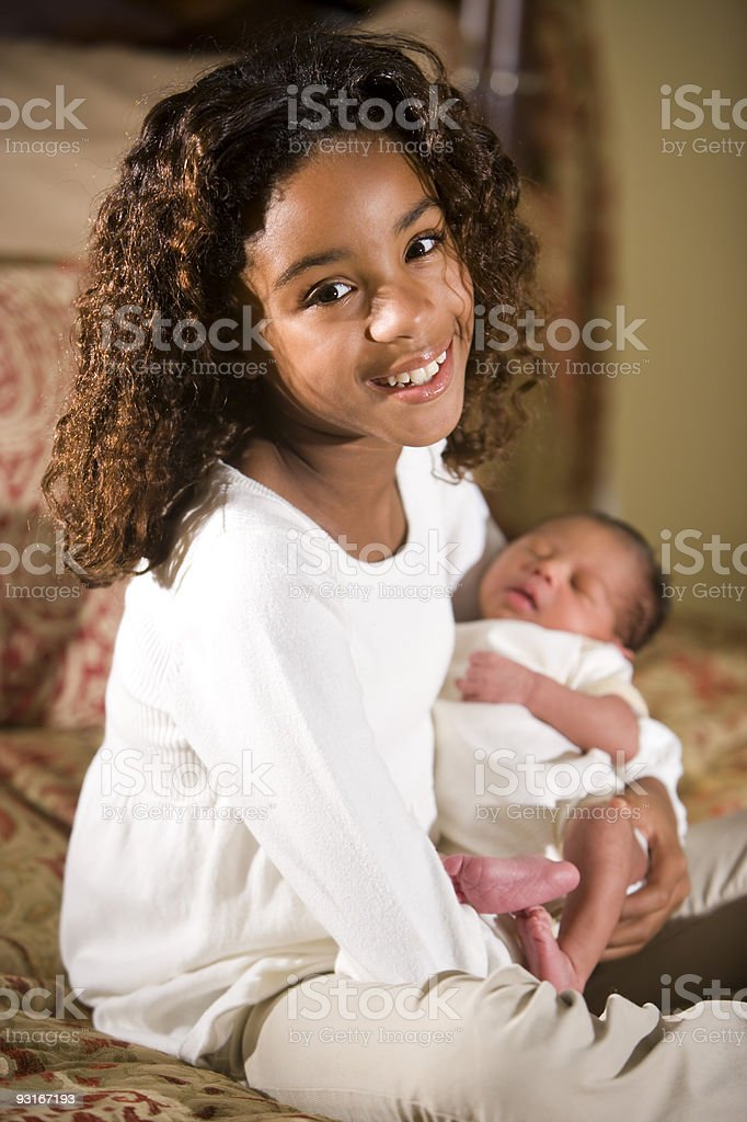 African American child holding tiny newborn baby stock photo