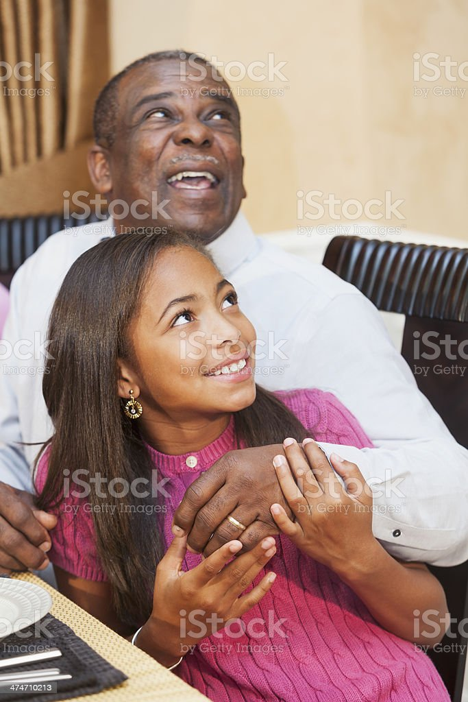 African American child with grandparent at dinner table stock photo