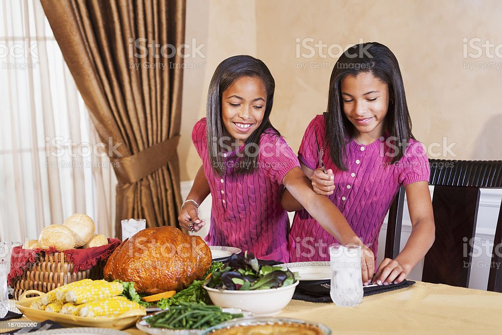 African American children setting the table for holiday dinner stock photo
