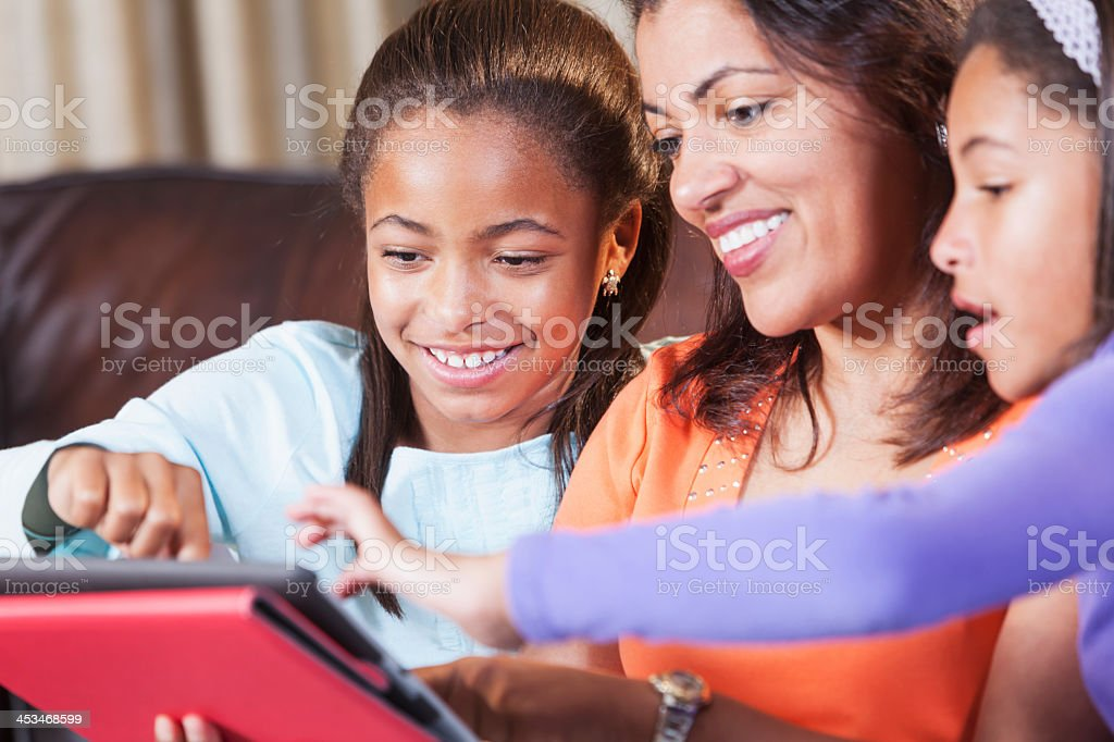 African American children teaching parent how to use digital tablet stock photo