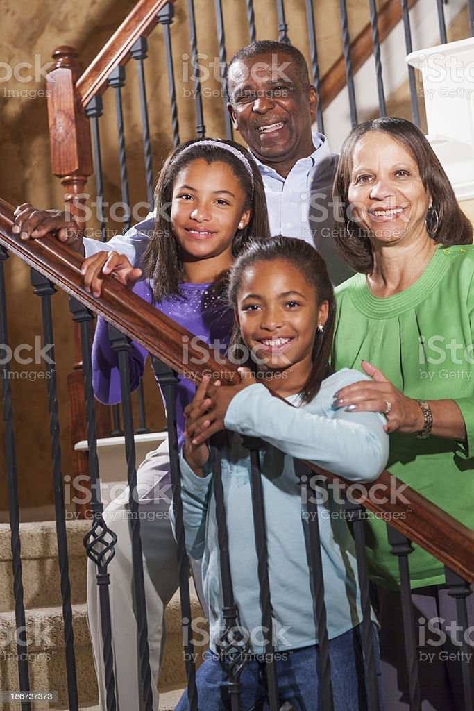 African American children with grandparents at home on stairs stock photo