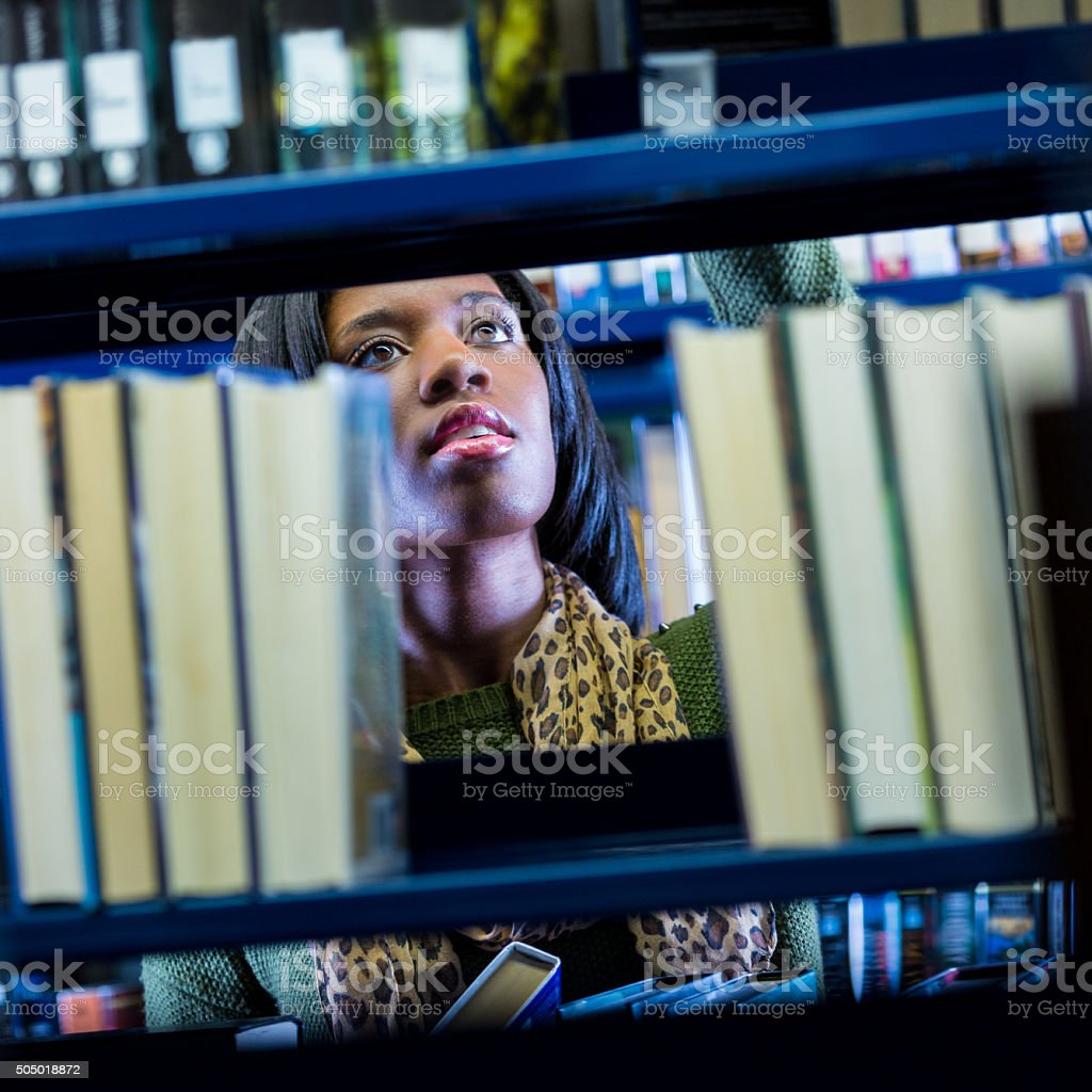 African American college student searching for library book on shelf stock photo