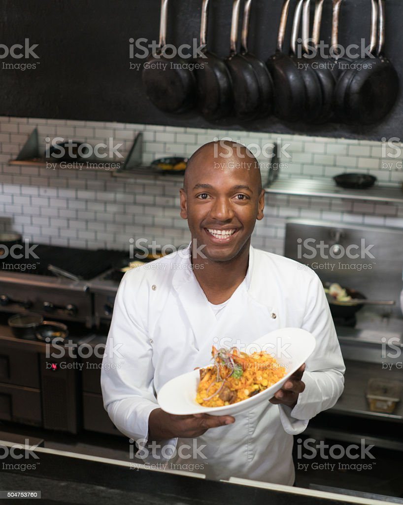 African American cook showing plate to the camera stock photo