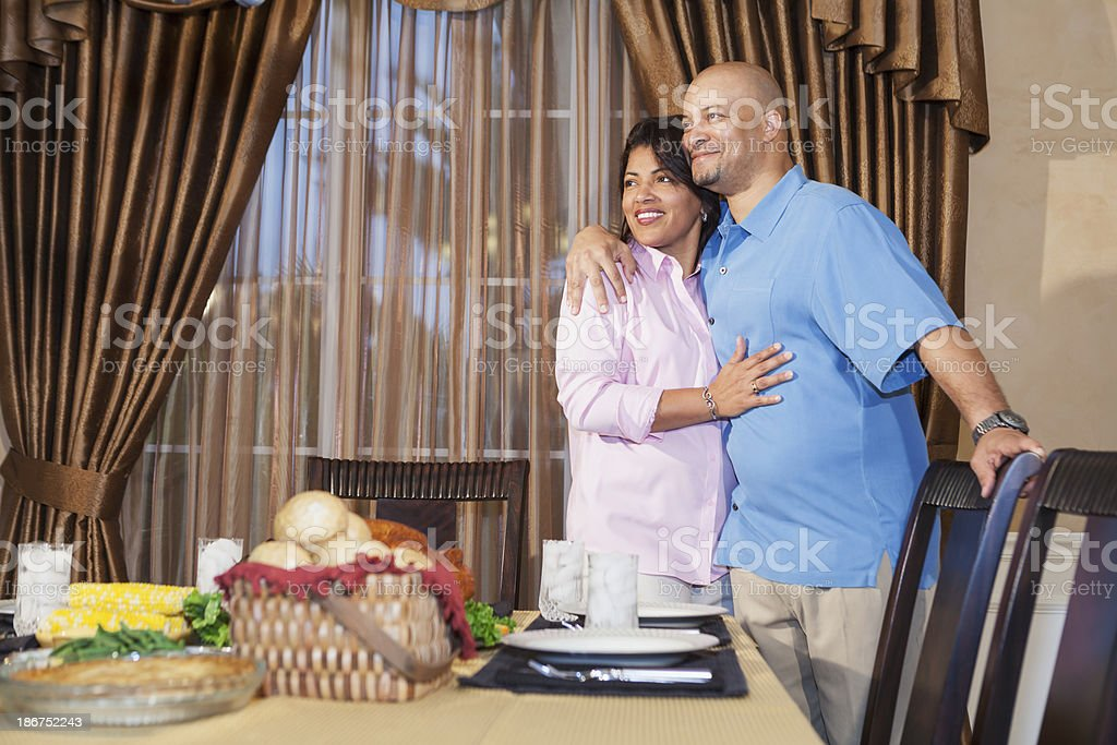 African American couple in dining room, table set for dinner stock photo