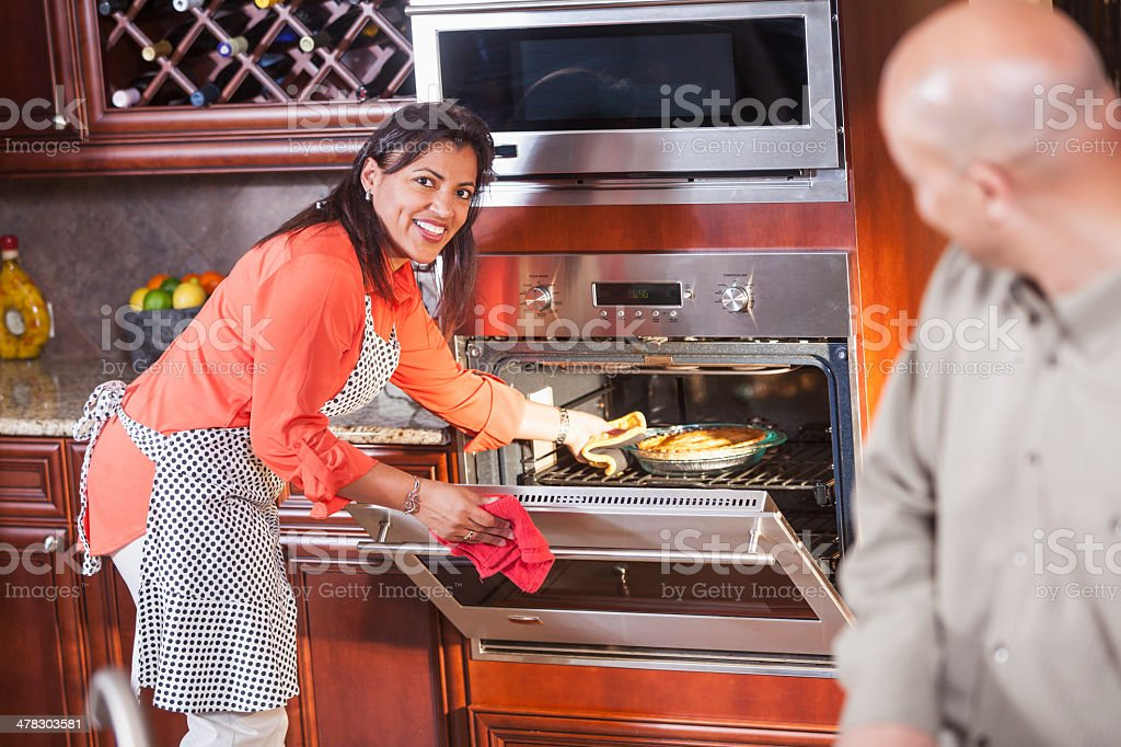 African American couple in kitchen, wife baking a pie stock photo