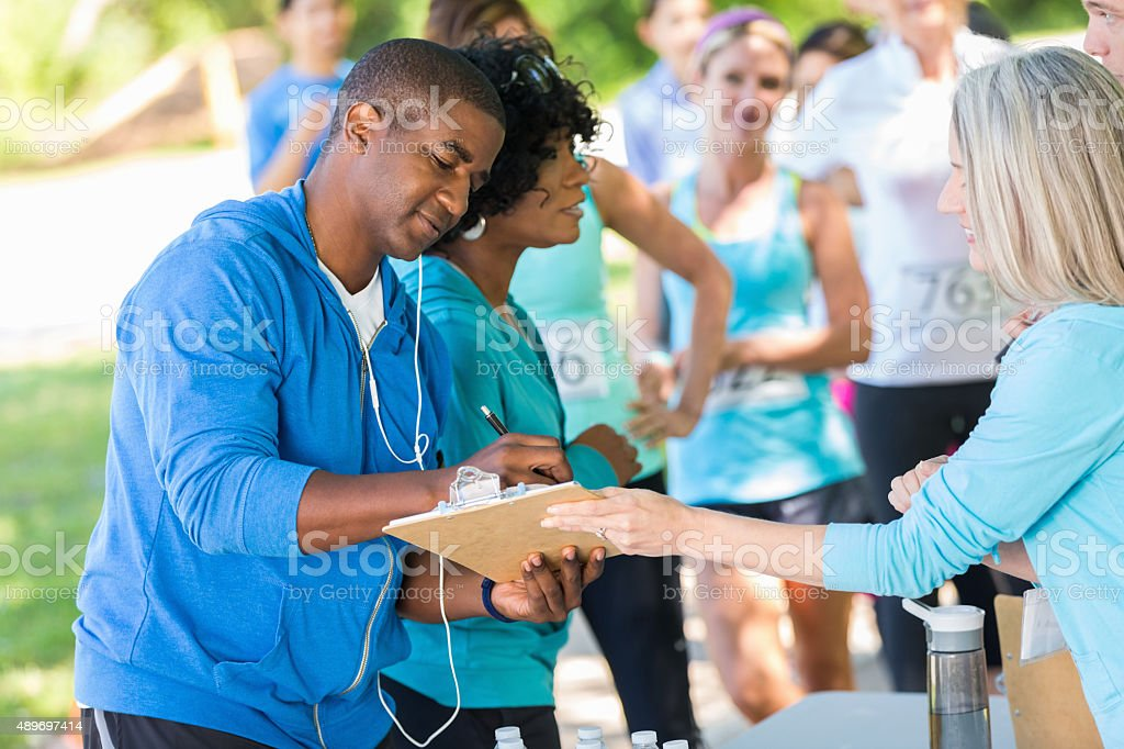 African American couple registering for marathon or 5k race stock photo