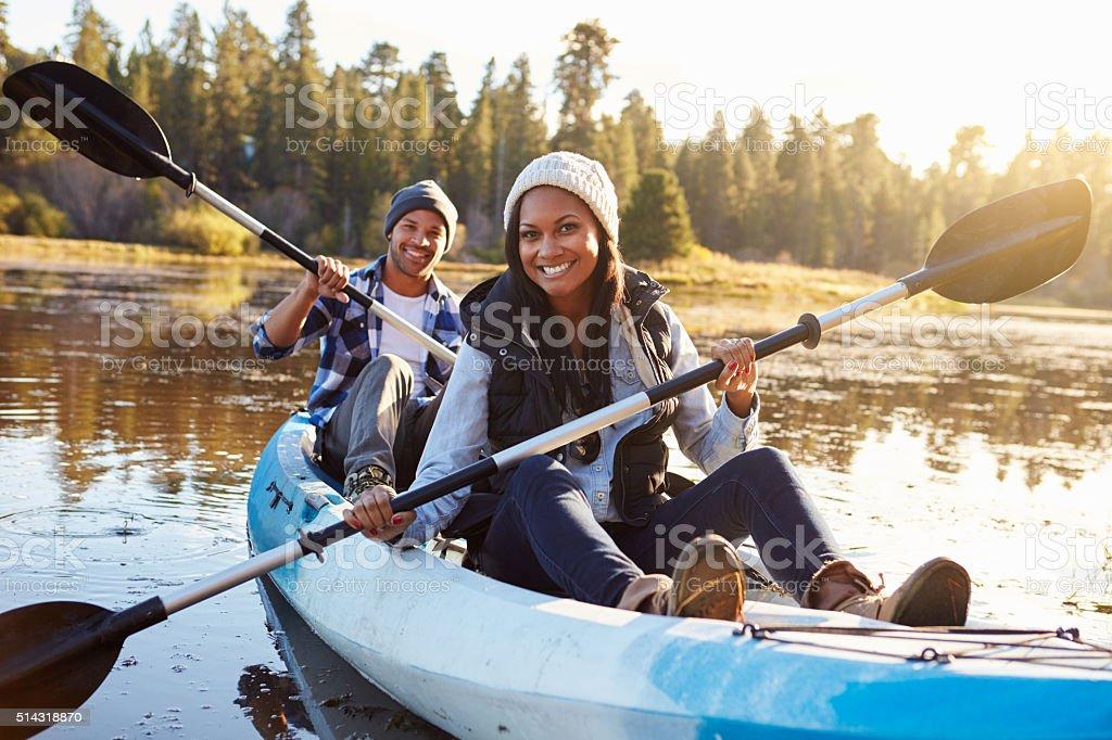 African American Couple Rowing Kayak On Lake stock photo