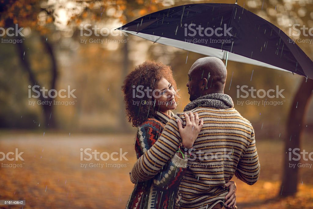 African American couple under umbrella during rainy autumn day. stock photo