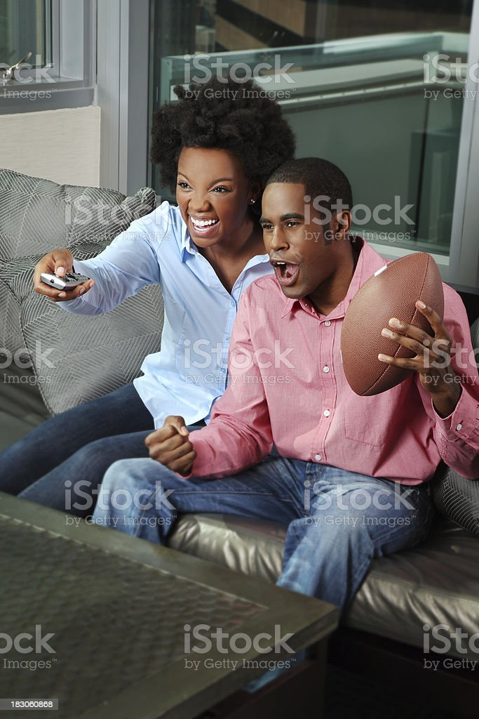 African American Couple Watching Football on TV royalty-free stock photo