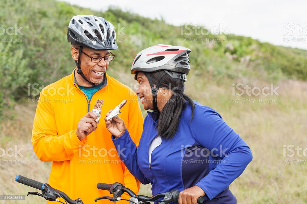 African American couple with bikes, eating snack stock photo