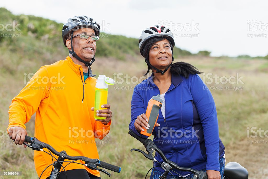 African American couple with bikes, water bottles stock photo