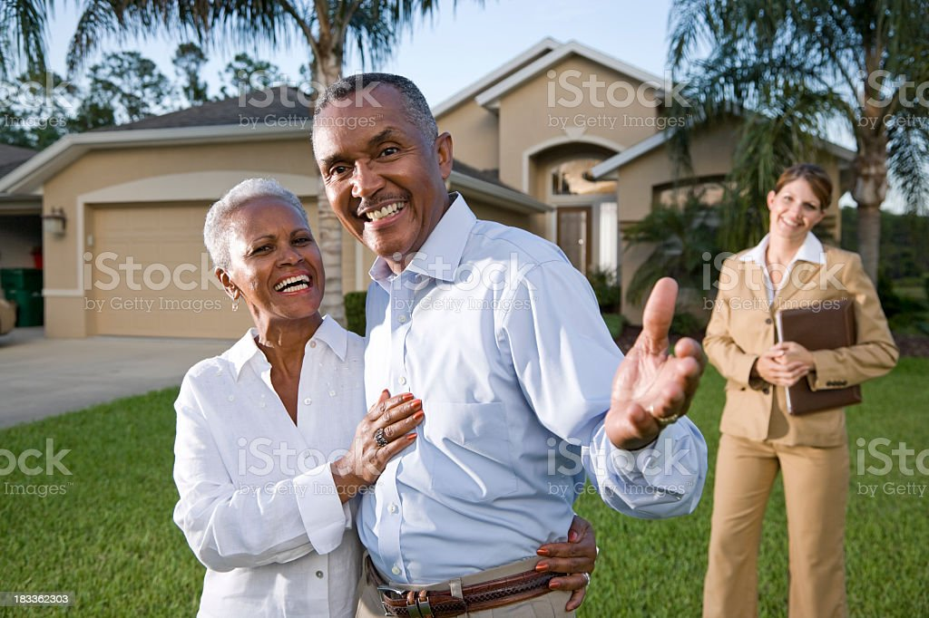 African American couple with real estate agent outside house stock photo