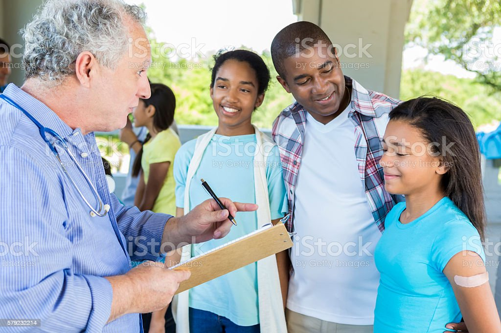 African American Dad and daughters at free flu shot clinic stock photo