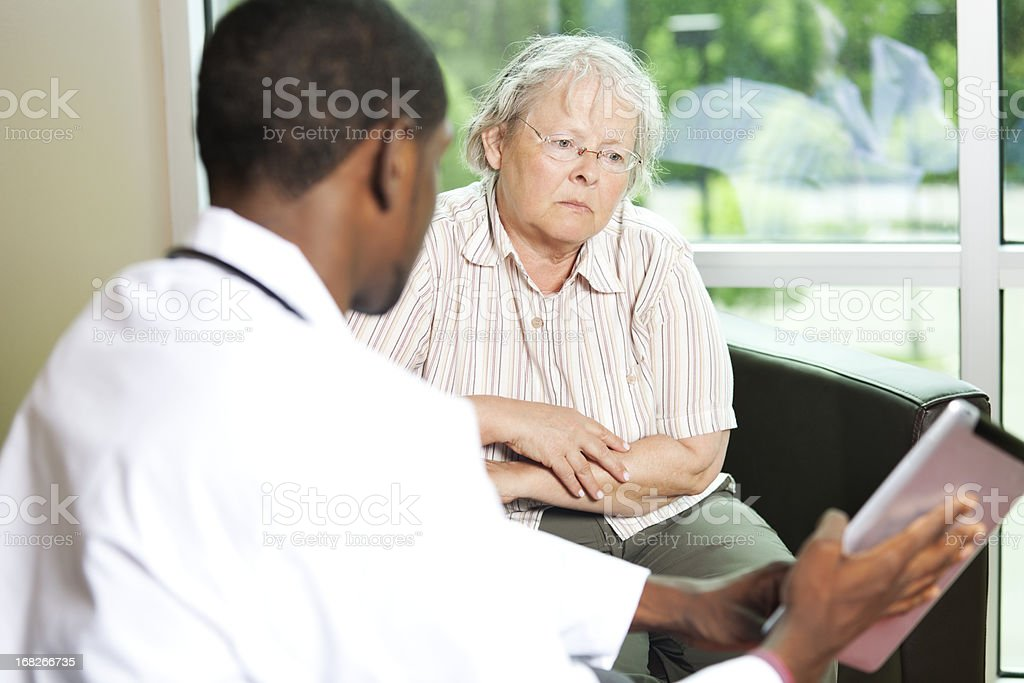 African american doctor consulting with a senior woman royalty-free stock photo
