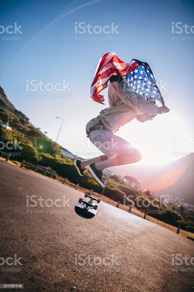 African American doing Ollie while Holding American Flag on Road stock photo