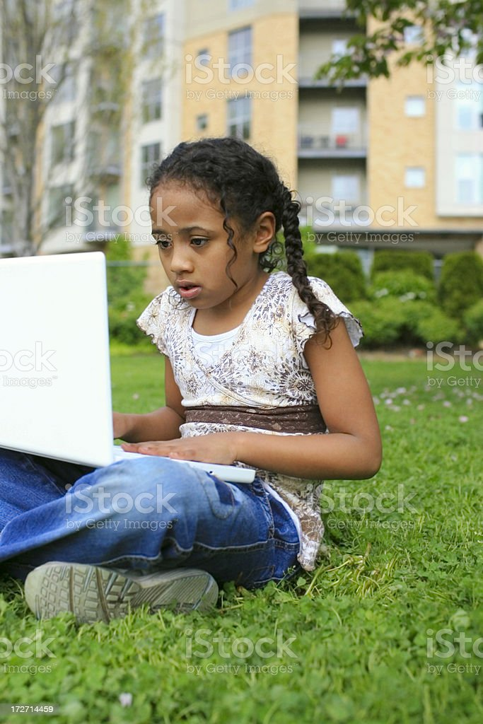African American Elementary Age Girl Using Laptop on Grass Outdoors royalty-free stock photo