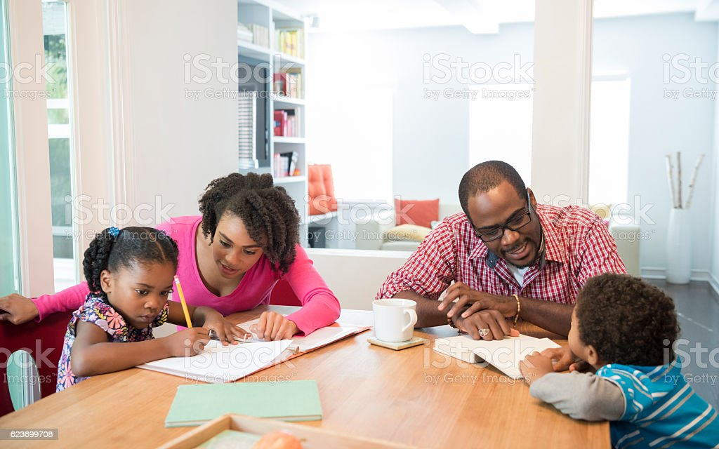 African American family at home, children doing homework stock photo