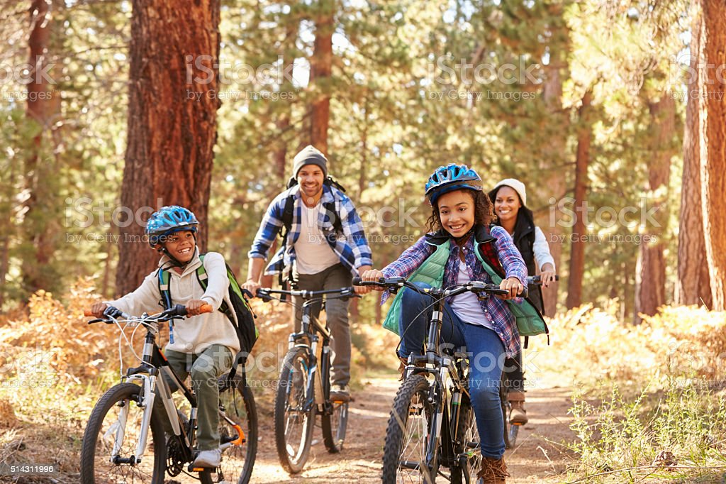 African American Family Cycling Through Fall Woodland stock photo