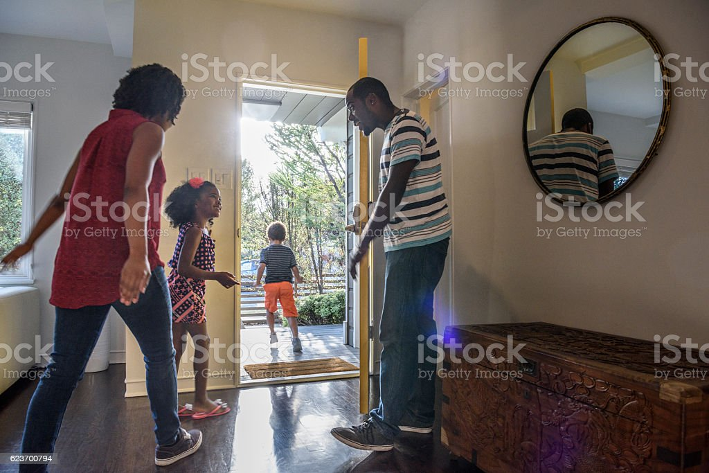 African American family leaving the house, father holding door stock photo