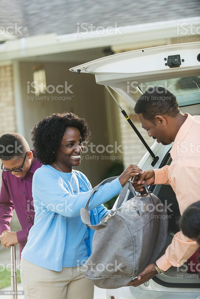 African American family loading luggage into car stock photo