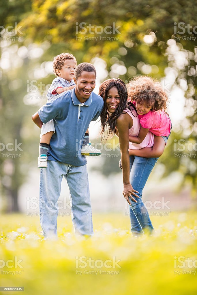 African American family piggybacking outdoors. stock photo