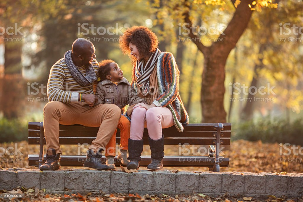 African American family relaxing on bench in the autumn park. stock photo