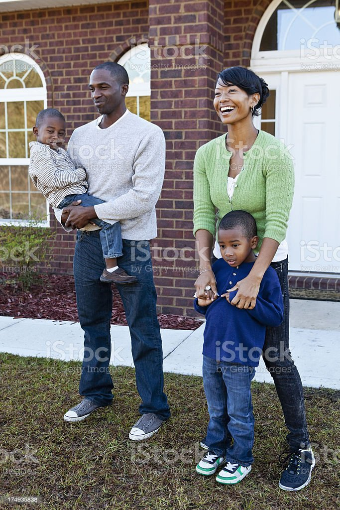 African American family standing in front of house stock photo