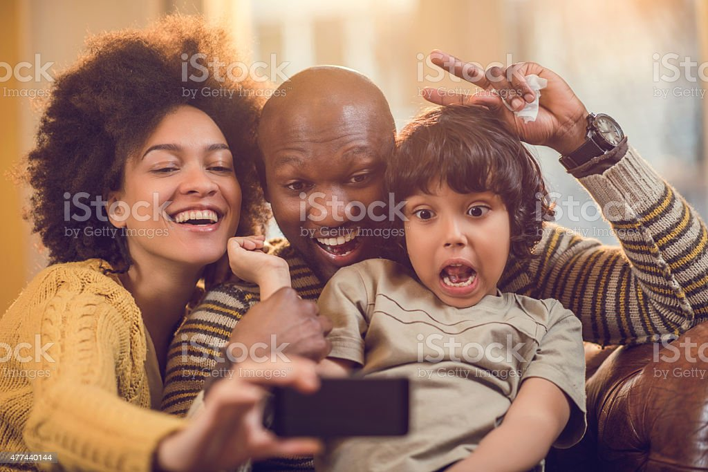 African American family taking a funny selfie with mobile phone. stock photo