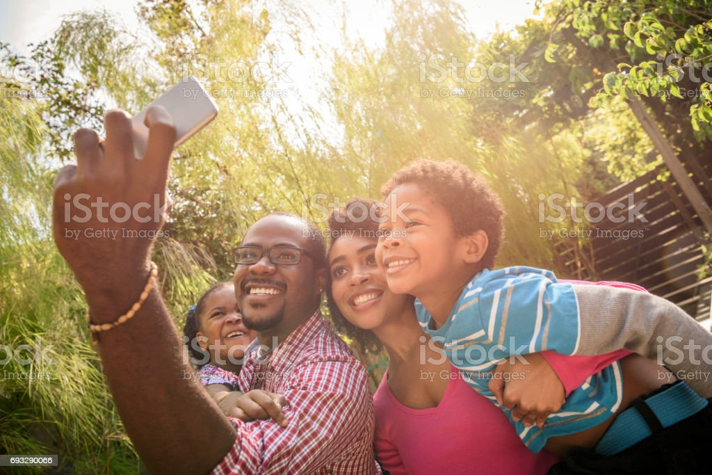 African American family taking selfie with phone stock photo