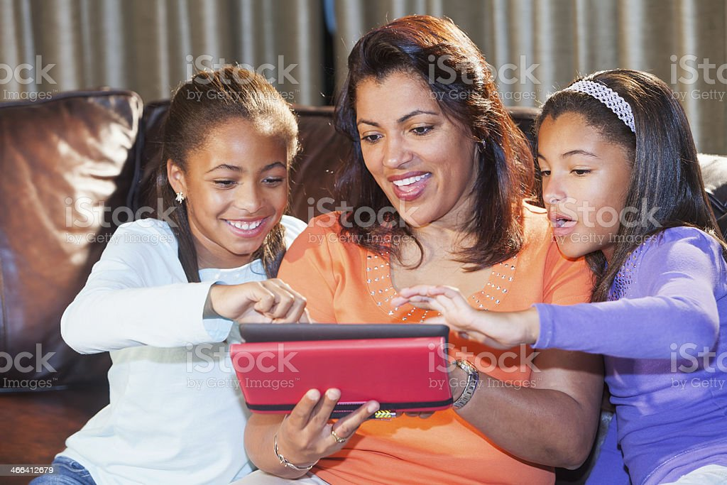 African American family using digital tablet together at home stock photo