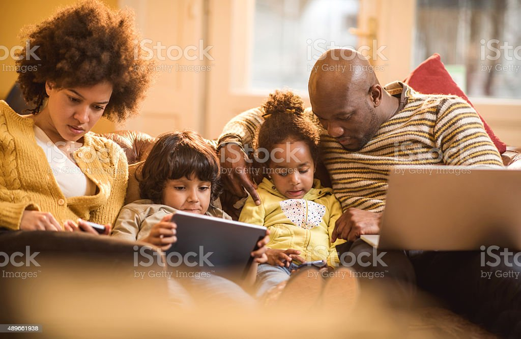 African American family using wireless technology at home. stock photo