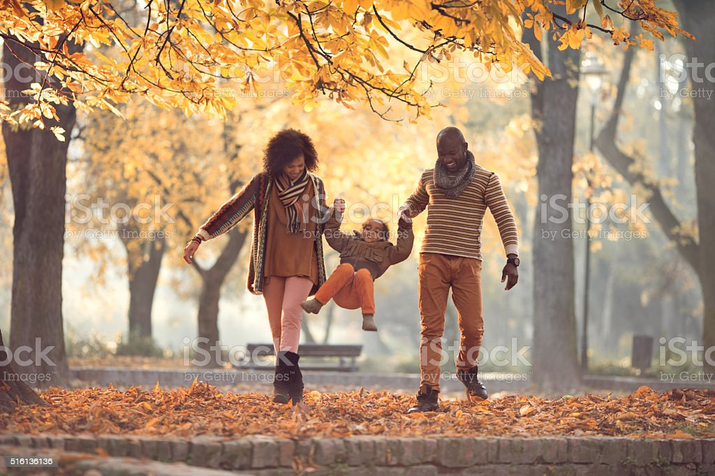 African American family walking and having fun in autumn park. stock photo