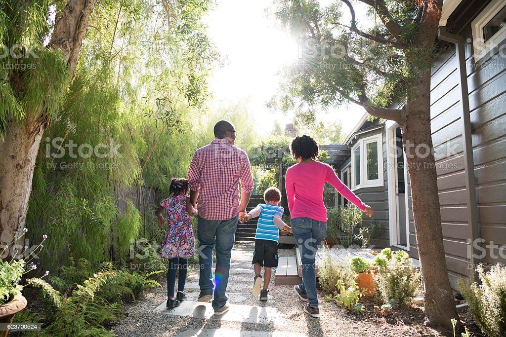 African American family walking in garden, rear view stock photo