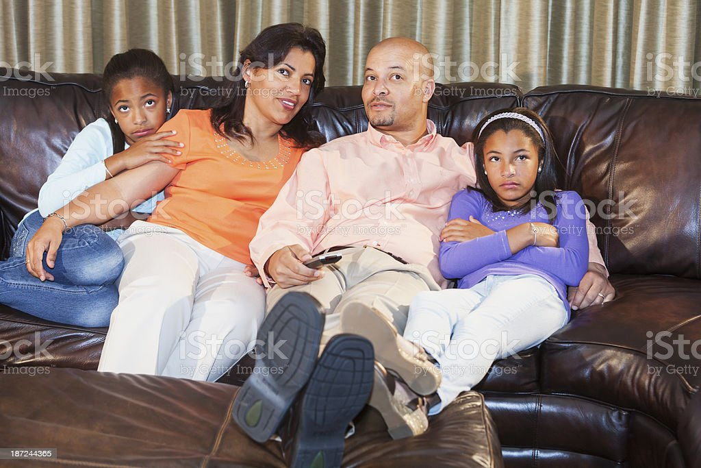 African American family watching television at home on couch stock photo